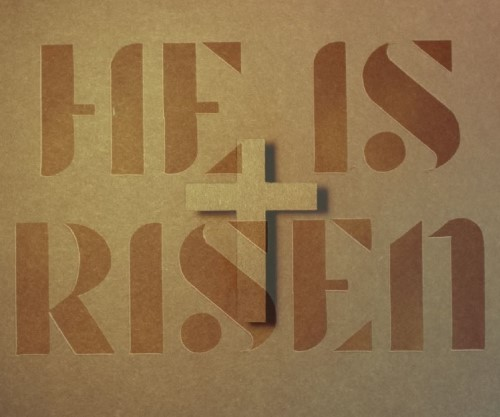 The text 'He is risen' silhouetting a crucifixion cross
